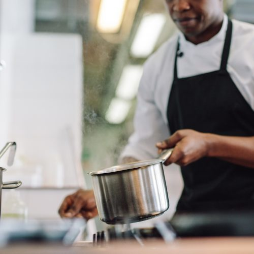 Cropped shot of chef putting cooking pot on stove. Chef cooking food at commercial kitchen.